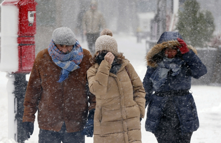 Pedestrians make their way through blowing snow during a snowstorm, Tuesday, March 13, 2018, in Boston. (AP Photo/Michael Dwyer)