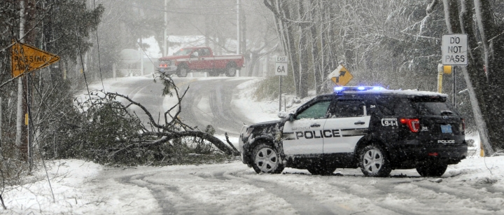 Sandwich Police block Route 6A at the Quaker Meetinghouse intersection where a tree downed live wires during a snowstorm, Tuesday, March 13, 2018 in Sandwich, Mass. (Steve Heaslip/The Cape Cod Times via AP)