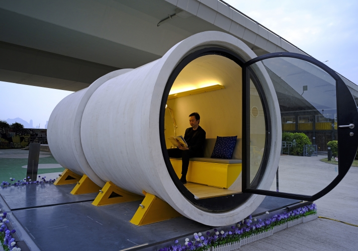 In this Tuesday, March 13, 2018, photo, architect James Law sits at an OPod tube house in Hong Kong's industrial area of Kwun Tong. Hong Kong's notoriously expensive housing makes owning an affordable home a pipe dream for many residents. But the local architect proposed a novel idea to help alleviate the problem: building stylish micro-apartments inside giant concrete drainage pipes. (AP Photo/Vincent Yu)