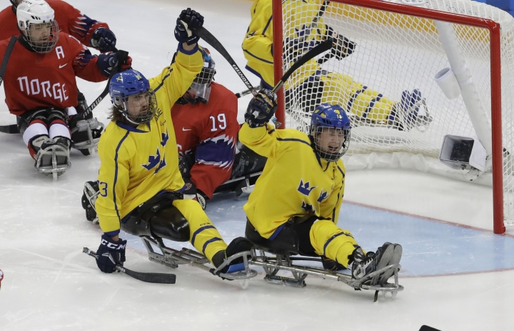 Sweden's Maximilian Gyllsten, left, celebrates after scoring against Norway during a preliminary round of the ice hockey game at the 2018 Winter Paralympics in Gangneung, South Korea, Tuesday, March 13, 2018. (AP Photo/Lee Jin-man)