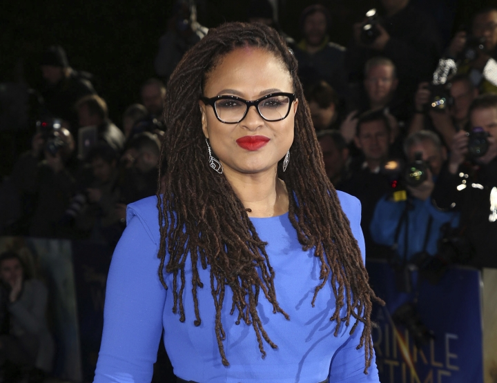 """FILE - In this March 13, 2018 file photo, director Ava DuVernay poses for photographers at the premiere of the film """"A Wrinkle In Time,"""" in London. Warner Bros. said Thursday that DuVernay will direct """"The New Gods,"""" a DC Comics property created by the famed comic book artist Jack Kirby. It's an elaborate science fiction work, part of Kirby's """"Fourth World Saga,"""" about two warring alien planets. It debuted in 1971. (Photo by Joel C Ryan/Invision/AP, File)"""