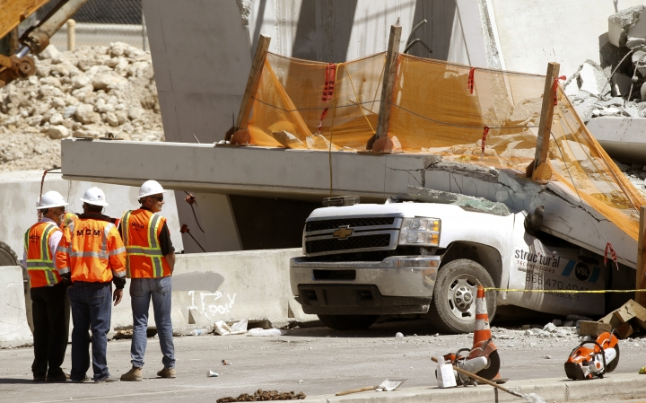 Workers stand next to a section of a collapsed pedestrian bridge, Friday, March 16, 2018 near Florida International University in the Miami area. The new pedestrian bridge that was under construction collapsed onto a busy Miami highway Thursday afternoon, crushing vehicles beneath massive slabs of concrete and steel, killing and injuring several people, authorities said. (AP Photo/Wilfredo Lee)