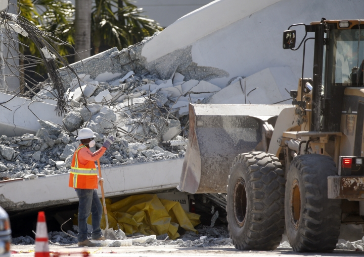 Workers use a front loader to clear debris from a section of a collapsed pedestrian bridge, Friday, March 16, 2018 near Florida International University in the Miami area. The new pedestrian bridge that was under construction collapsed onto a busy Miami highway Thursday afternoon, crushing vehicles beneath massive slabs of concrete and steel, killing and injuring several people, authorities said. (AP Photo/Wilfredo Lee)