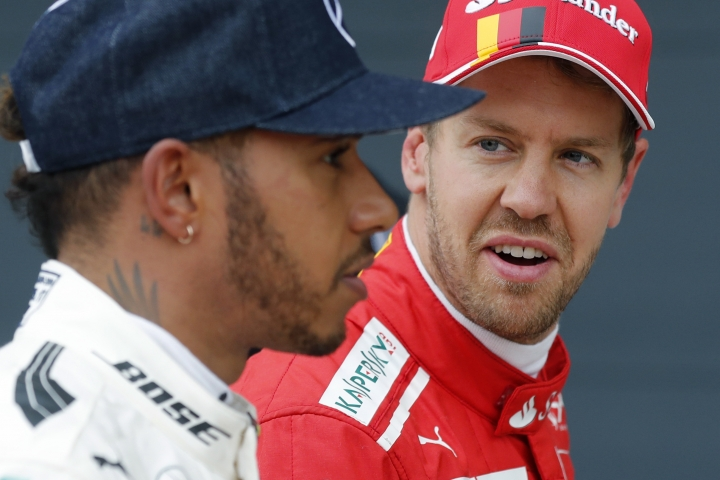 FILE - In this Saturday, July 15, 2017 file photo, Ferrari driver Sebastian Vettel of Germany, right, looks at Mercedes driver Lewis Hamilton of Britain after the qualifying session for the British Formula One Grand Prix at the Silverstone racetrack in Silverstone, England. Hamilton and Vettel start the Formula One season within touching distance of further greatness. A fifth world title would move one of them level with Juan Manuel Fangio and second only to Michael Schumacher's seven. (AP Photo/Frank Augstein, File)