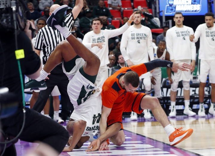 Michigan State forward Nick Ward (44) lands on his head after colliding with Bucknell guard Kimbal Mackenzie (1) during the second half of an NCAA men's college basketball tournament first-round game in Detroit, Friday, March 16, 2018. (AP Photo/Paul Sancya)