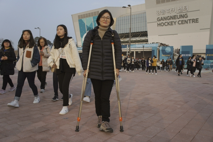 In this March 12, 2018, photo, South Korean Park Mi-ae poses in front of the Gangneung Hockey Center in Gangneung, South Korea. Park, a 53-year-old Gangneung resident who came to a hockey game on crutches while recovering from a foot injury, hoped that the experience of accommodating a large number of disabled people and athletes will help make her city a safer and friendlier place for the disabled. The thousands from across the country who volunteered for the games could help initiate changes at their homes too, she said. (AP Photo/Kim Tong-hyung)