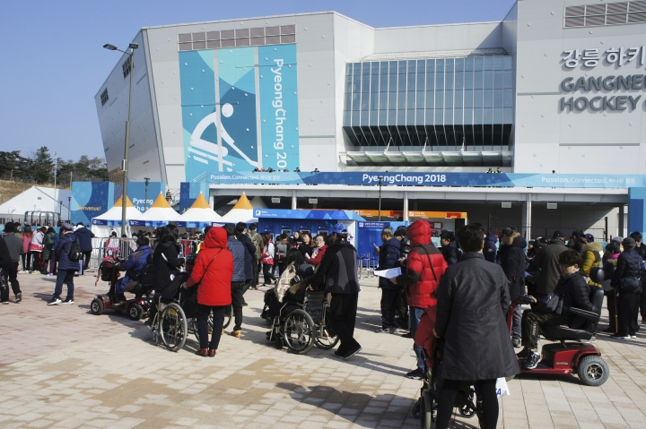 In this March 11, 2018, photo, people in wheelchairs wait to enter the Gangneung Hockey Center in Gangneung, South Korea. When the Paralympics ended Sunday, March 18 with the closing ceremony at the soon-to-be-demolished Olympic Stadium, South Korea faced questions about the event's legacy. (AP Photo/Kim Tong-hyung)