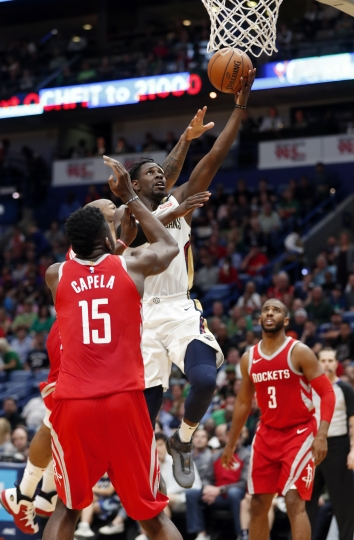 New Orleans Pelicans guard Jrue Holiday (11) goes to the basket in front Houston Rockets center Clint Capela (15) during the second half of an NBA basketball game in New Orleans, Saturday, March 17, 2018. The Rockets won 107-101. (AP Photo/Gerald Herbert)