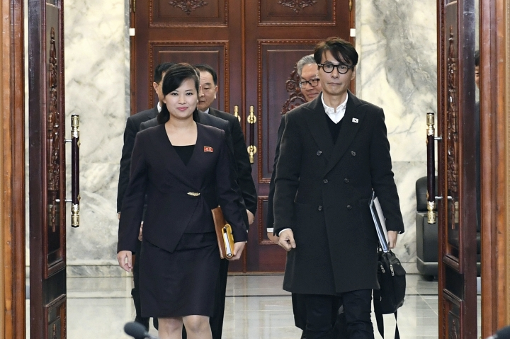 In this photo provided by South Korea Unification Ministry, North Korean Hyon Song Wol, left, head of a North Korean art troupe, walks with her South Korean counterpart Yun Sang to hold a meeting to discuss a South Korean art troupe's planned performance in Pyongyang, North Korea, at the North side of Panmunjom, North Korea, Tuesday, March 20, 2018. (South Korea Unification Ministry via AP)