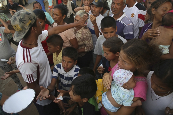 In this March 8, 2018 photo, Venezuelans wait for a free meal in Simon Bolivar Square where many are living in tents in Boa Vista, Roraima state, Brazil. When trucks pull up with food, hundreds run toward them to get a meal before they run out, while tempers flare as men accuse women and children of using their advantage to get extra portions. (AP Photo/Eraldo Peres)