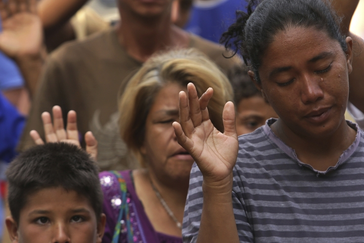 In this March 11, 2018 photo, a tear runs down the cheek of Venezuelan woman praying during religious service in Simon Bolivar Square where many are living in tents in Boa Vista, Roraima state, Brazil. While in recent years millions of Venezuelans have immigrated, until recently Brazil received relatively few of them. Hundreds of thousands have gone to Colombia, but authorities there and elsewhere in South America are tightening their borders. (AP Photo/Eraldo Peres)