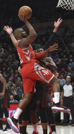 Houston Rockets guard Chris Paul drives to the basket on Portland Trail Blazers guard Damian Lillard during the first half of an NBA basketball game in Portland, Ore., Tuesday, March 20, 2018. (AP Photo/Steve Dykes)