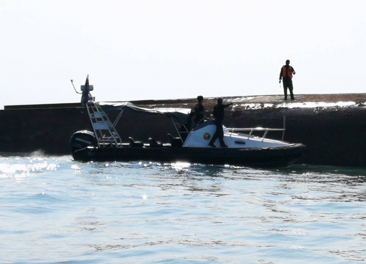This photo released by Malaysian Maritime Enforcement Agency shows a capsized sand-dredging vessel is seen in the waters near Muar, Johor, Malaysia, Wednesday, March 21, 2018. Malaysia's coast guard says a Chinese sand-dredger capsized off the country's southern coast, killing a crew member and leaving 14 others still missing. (Malaysian Maritime Enforcement Agency via AP)