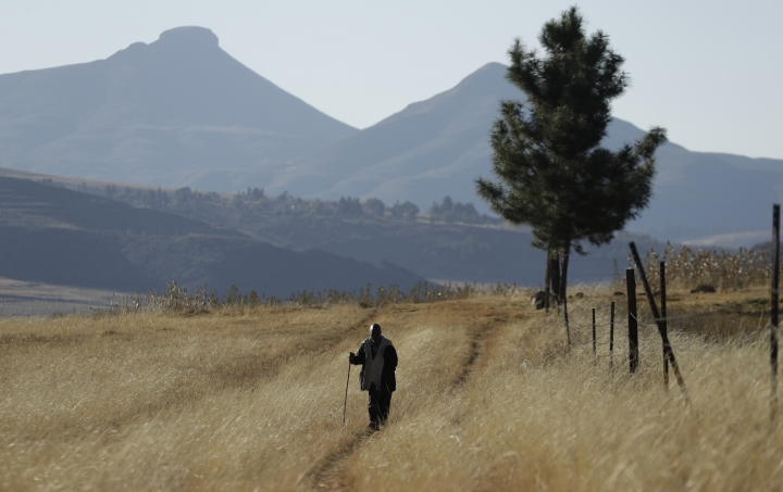 "FILE - In this June 3, 2017, file photo, a man walks on the land at Ha Mampho village, Lesotho. The blockbuster film ""Black Panther"" has created a new compelling vision of Africa as a continent of smart, technologically savvy people with cool clothes living in a futuristic city amid stunning landscapes. (AP Photo/Themba Hadebe, File)"