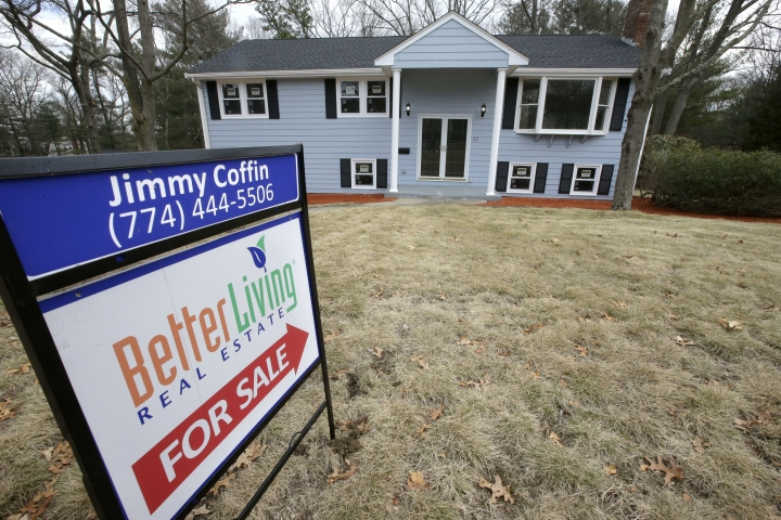 FILE- In this Feb. 23, 2018, file photo a for sale sign stands in front of a house in Walpole, Mass. On Wednesday, March 21, the National Association of Realtors reports on February sales of existing homes. (AP Photo/Steven Senne, File)