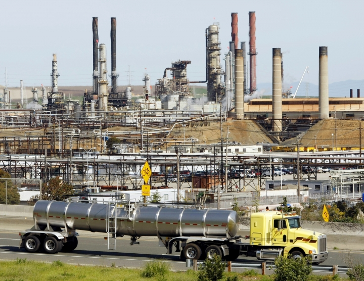 "FILE - This March 9, 2010 file photo shows a tanker truck passing the Chevron oil refinery in Richmond, Calif. A federal judge presiding over lawsuits accusing big oil companies of lying about global warming is turning his courtroom into a classroom. U.S. District Judge William Alsup has asked lawyers for two California cities and five of the world's largest oil and gas companies to come to court on Wednesday, March 21, 2018 to present ""the best science now available on global warming."" (AP Photo/Paul Sakuma, File)"