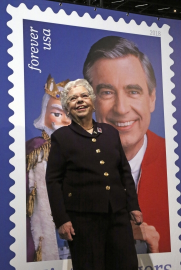 Mrs. Joanne Rogers, wife of the late Fred Rogers, stands in front of a giant Mister Rogers Forever Stamp following the first-day-of-issue dedication in WQED's Fred Rogers Studio in Pittsburgh, Friday, March 23, 2018. (AP Photo/Gene J. Puskar)