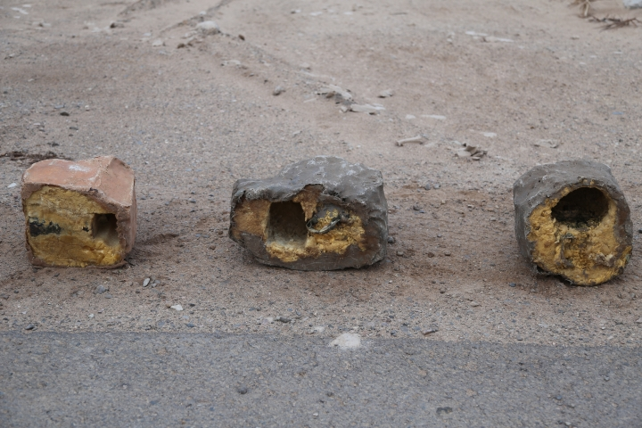 In this undated photograph provided by Conflict Armament Research, an independent London-based group that researches battlefield weaponry, three explosives disguised as rocks are on display in Yemen. Roadside bombs disguised as rocks in Yemen bear similarities to others used by Hezbollah in southern Lebanon and by insurgents in Iraq and Bahrain, suggesting at the least an Iranian influence in their manufacturing, a report released Monday, March 26, 2018, by Conflict Armament Research alleges. The report comes comes as the West and United Nations researchers accuse Iran of supplying arms to Yemen's Shiite rebels known as Houthis, who have held the country's capital since September 2014. (Tim Michetti/Conflict Armament Research via AP)