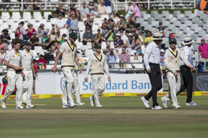 Steven Smith of Australia, center, takes to the field with the team on the fourth day of the third cricket test between South Africa and Australia at Newlands Stadium, in Cape Town, South Africa, Sunday, March 25, 2018. (AP Photo/Halden Krog)