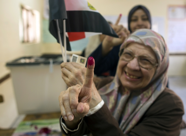 Magdah Ahmed, 78, displays her inked finger after she casts her vote at a polling station during the first day of the presidential election at a polling station in Cairo, Egypt, Monday, March 26, 2018. Polls have opened in Egypt's presidential election with the outcome _ a second term for President Abdel-Fattah el-Sissi _ a foregone conclusion. (AP Photo/Amr Nabil)