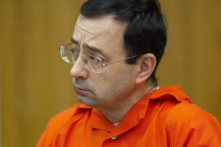 FILE - In this Jan. 31, 2018, file photo, Larry Nassar appears for his sentencing at Eaton County Circuit Court in Charlotte, Mich. William Strampel, a high-ranking Michigan State University official, has been arrested amid an investigation into the handling of complaints against now-imprisoned former sports doctor Nassar. Ingham County Sheriff Scott Wriggelsworth told The Associated Press that Strampel was in custody at the jail Monday night, March 26, 2018. (Cory Morse/The Grand Rapids Press via AP, File)