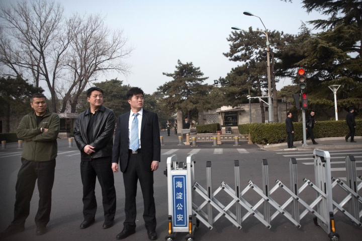 Plainclothes security officials block a road in front of the Diaoyutai State Guesthouse in Beijing, Tuesday, March 27, 2018. Unusually heavy security at a Beijing guesthouse where prominent North Koreans have stayed in the past and media reports of a special train arriving have raised speculation that Kim Jong Un is making his first trip to China as the North's leader. (AP Photo/Mark Schiefelbein)