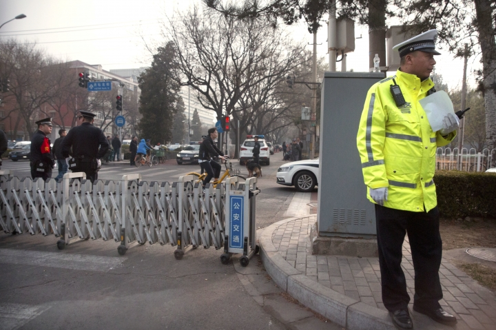 Chinese policemen stand guard at a road barricade in front of the Diaoyutai State Guesthouse in Beijing, Tuesday, March 27, 2018. Unusually heavy security at a Beijing guesthouse where prominent North Koreans have stayed in the past and media reports of a special train arriving have raised speculation that Kim Jong Un is making his first trip to China as the North's leader. (AP Photo/Mark Schiefelbein)