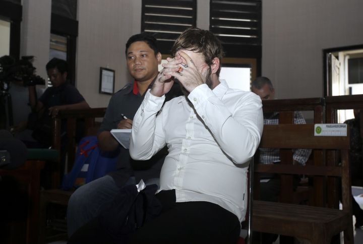 Australian Joshua Baker covers his face as he sits in a courtroom during his verdict trial in Bali, Indonesia, Tuesday, March, 27, 2018. Indonesian judges sentenced Baker to ten months in rehabilitation on allegations for trying to smuggle illegal drugs on to the island. (AP Photo/Firdia Lisnawati)