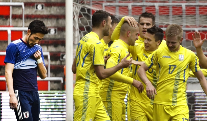 Ukraine's Yaroslav Rakitskiy, center left, is congratulated after scoring his sides first goal during an international friendly soccer match between Japan and Ukraine at Maurice Dufrasne Stadium in Liege, Belgium on Tuesday, March 27, 2018. (AP Photo/Olivier Matthys)