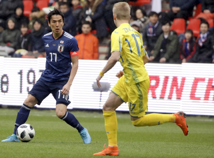 Japan's Makoto Hasebe, left, is challenged by Ukraine's Oleksandr Zinchenko during a friendly soccer match between Japan and Ukraine at Maurice Dufrasne Stadium in Liege, Belgium on Tuesday, March 27, 2018. (AP Photo/Olivier Matthys)
