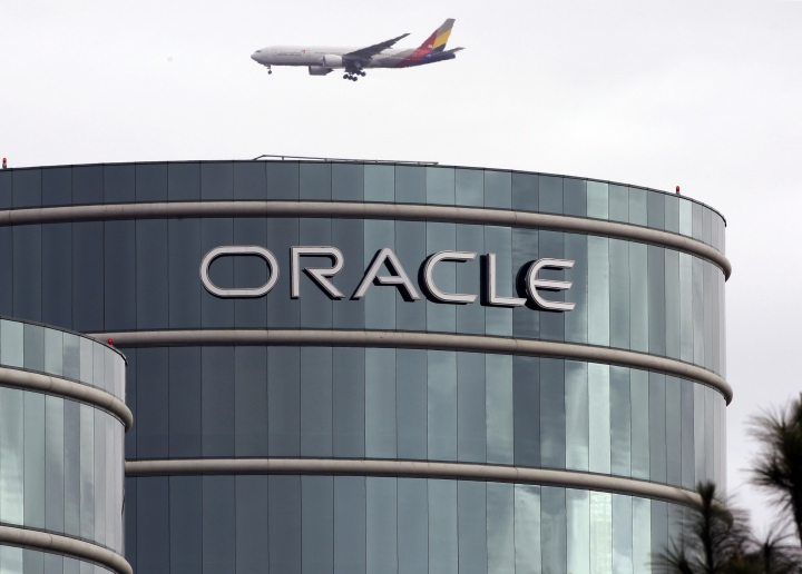 FILE - In this March 20, 2012, file photo, a plane flies over Oracle headquarters in Redwood City, Calif. On Tuesday, March 27, 2018, a federal appeals court overturned a decision in a long-running legal battle over whether Google infringed on Oracle's Java programming language to build its hugely popular mobile operating system, Android. (AP Photo/Paul Sakuma, File)