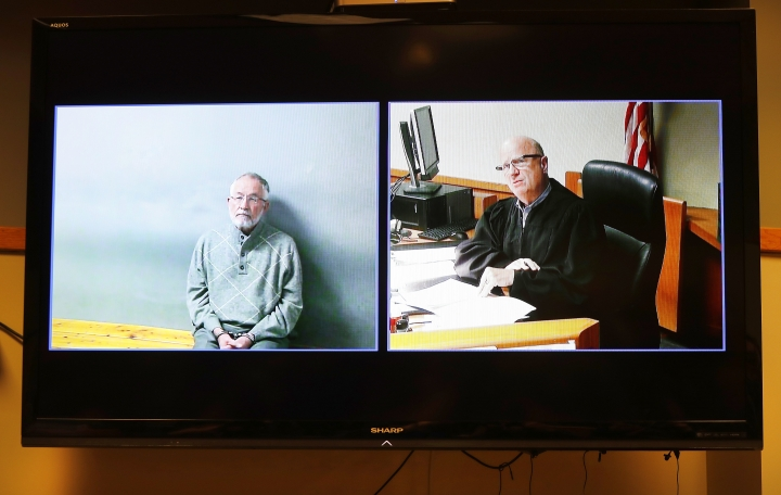 William Strampel, left, appears during his video arraignment, with Judge Richard D. Ball, right, Tuesday, March 27, 2018, in East Lansing, Mich. Strampel, a Michigan State University official who oversaw Larry Nassar, was arrested Monday amid an investigation into the handling of complaints against the former sport doctor, who is in prison for sexually assaulting patients under the guise of treatment. (AP Photo/Paul Sancya)