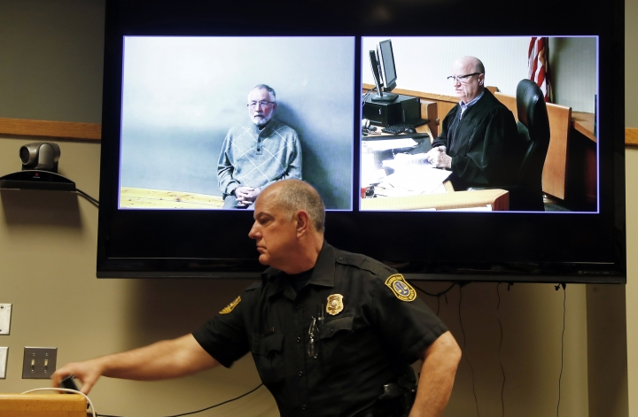 A court officer works in the courtroom as William Strampel, left, appears during his video arraignment with Judge Richard D. Ball, Tuesday, March 27, 2018, in East Lansing, Mich. Strampel, a Michigan State University official who oversaw Larry Nassar, was arrested Monday amid an investigation into the handling of complaints against the former sport doctor, who is in prison for sexually assaulting patients under the guise of treatment. (AP Photo/Paul Sancya)