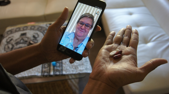 In this March 15, 2018 photo, public health nurse Peggy Cooley of the Tacoma-Pierce County Health Department, seen on the phone screen, uses Skype video to remotely monitor a patient taking antibiotics for tuberculosis at home in Lakewood, Wash. Researchers are testing how well smartphone apps that monitor pill-taking work when medication matters. Experts praise the efficiency, but some say the technology raises privacy and data security concerns. (AP Photo/Manuel Valdes)