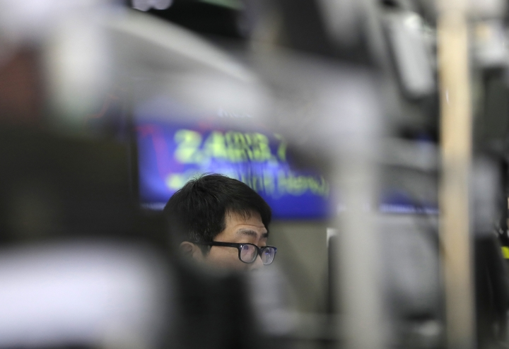 A currency trader watches computer monitors at the foreign exchange dealing room in Seoul, South Korea, Wednesday, March 28, 2018. Asian stock markets were in the red Wednesday as tech stocks extended losses following sell-offs of their U.S. peers overnight. Investors are selling technology-related shares on concern governments might tighten their scrutiny over Facebook after it was revealed that users' data was shared with a consulting firm affiliated with President Donald Trump. (AP Photo/Lee Jin-man)