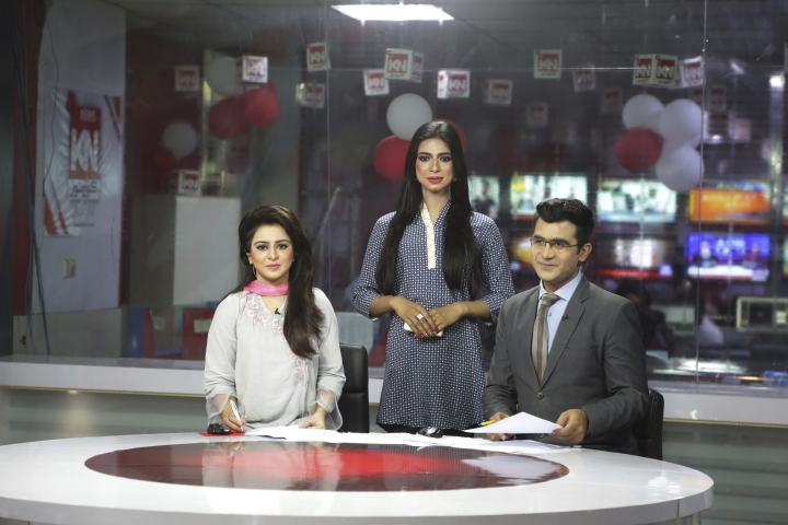 In this photo taken on Tuesday, March 27, 2018, Pakistan's first transgender newscaster Marvia Malik, center, stands with her colleagues at a local television channel in Lahore, Pakistan. Malik has made history in Pakistan by becoming the first transgender newscaster in a conservative Muslim country where her community is taunted in public, ostracized by family and targeted in violent attacks. (AP Photo/K.M. Chaudary)
