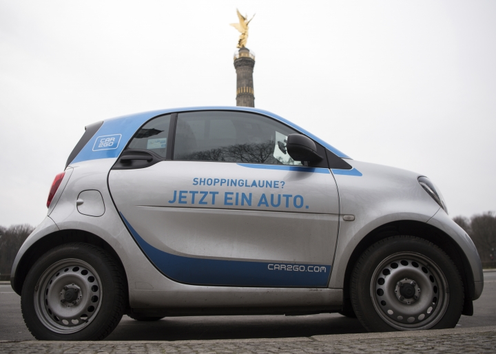 FILE In this Feb. 29, 2016 file photo a car2go car stands at the victory column in Berlin. Automakers Daimler and BMW have agreed Wednesday, March 28, 2018 to merge their transportation services businesses so they can expand their offerings in ride-hailing apps, car-sharing, parking and charging electric cars. Those businesses include car-sharing, an area where Stuttgart-based Daimler AG operates its car2go service and Munich-headquartered BMW AG has DriveNow. (Bernd von Jutrczenka/dpa via AP,file)