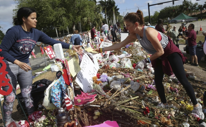 Patricia Padauy, right, passes a handwritten note to her friend Sharamy Angarita, as they clean and sort out items at the memorial site of Padauy's son Joaquin Oliver in Parkland, Fla., Wednesday, March 28, 2018. Volunteers, students and parents were sorting items left at the memorial sited for the 17 students and faculty killed at Marjory Stoneman Douglas High School on Valentine's Day. Flowers and plants will be composted while all other items will catalogued and saved. (AP Photo/Marta Lavandier)