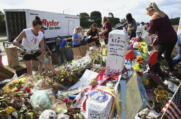 Volunteers, students and parents sort items left at the memorial site for the 17 students and faculty killed at Marjory Stoneman Douglas High School, Wednesday, March 28, 2018 in Parkland, Fla. Flowers and plants will be composted while all other items will be catalogued and saved. (AP Photo/Marta Lavandier)