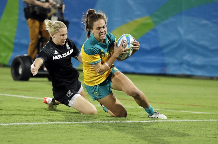 FILE - In this Aug. 8, 2016 file photo, Australia's Evania Pelite, right, scores a try as New Zealand's Kelly Brazier chasses during the women's rugby sevens gold medal match at the Summer Olympics in Rio de Janeiro, Brazil. More than 6,600 athletes and officials from across the world will converge on the Gold Coast for the 21st edition of the Commonwealth Games, the quadrennial multi-sports event for 71 countries and territories of the British Commonwealth. (AP Photo/Themba Hadebe,File)