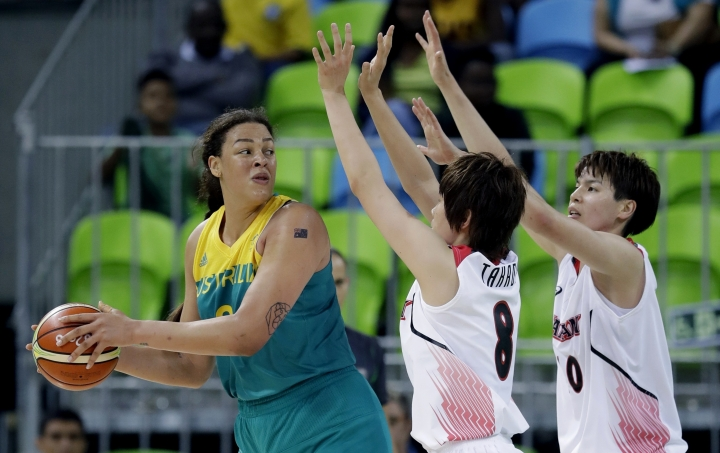 FILE - In this Aug. 11, 2016, file photo, Australia center Liz Cambage, left, looks to pass around Japan player's Maki Takada and Ramu Tokashiki, right, during their women's basketball game at the 2016 Summer Olympics in Rio de Janeiro, Brazil. More than 6,600 athletes and officials from across the world will converge on the Gold Coast for the 21st edition of the Commonwealth Games, the quadrennial multi-sports event for 71 countries and territories of the British Commonwealth. (AP Photo/Carlos Osorio, File)