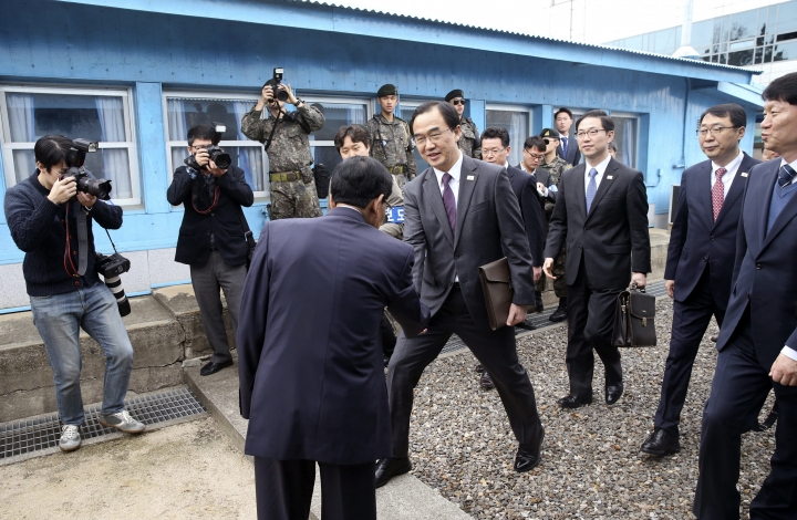 South Korean Unification Minister Cho Myoung-gyon, center, shakes hands with a North Korean official as he crosses to North Korea for the meeting at the northern side of the Panmunjom in North Korea, Thursday, March 29, 2018. High-level officials from North and South Korea began talks at a border village Thursday to prepare for an April summit between their leaders amid a global diplomatic push to resolve the standoff over the North's nuclear program. (Korea Pool via AP)