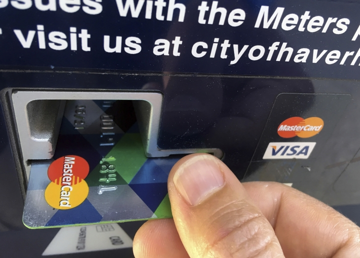 FILE- In this June 15, 2017, file photo a customer inserts a credit card to pay for parking in Haverhill, Mass. Car owners with poor credit can pay hundreds, if not thousands, more to drive than those with good credit. (AP Photo/Elise Amendola, File)
