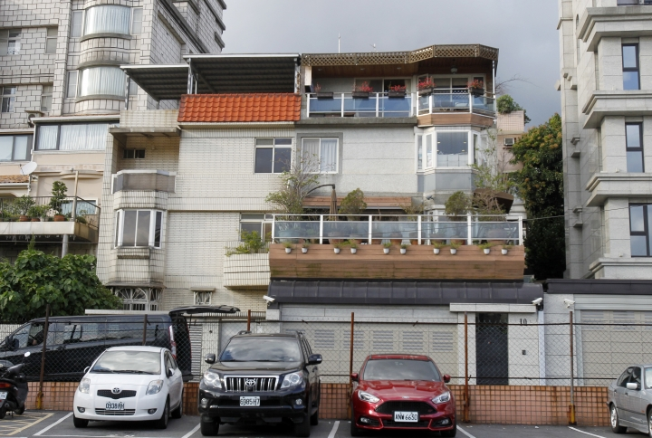 Cars are parked outside the home of An Tso Sun, the 18-year-old Taiwanese exchange student charged in the U.S. with threatening to shoot up his school in Taipei, Taiwan, Friday, March, 30 2018. (AP Photo/Chiang Ying-ying)