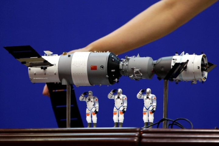 FILE PHOTO: A model of the Tiangong-1 space lab module (L), the Shenzhou-9 manned spacecraft (R) and three Chinese astronauts is displayed during a news conference at Jiuquan Satellite Launch Center, in Gansu province, China June 15, 2012.  REUTERS/Jason Lee/File Photo