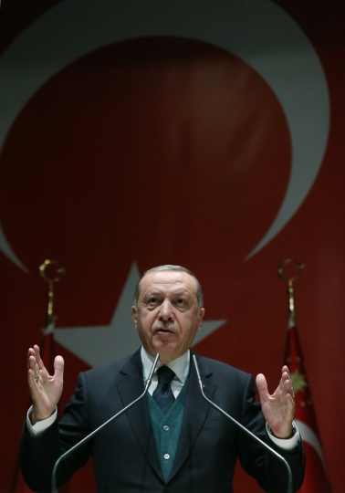 Turkey's President Recep Tayyip Erdogan gestures as he delivers a speech at his ruling Justice and Development (AKP) Party conference in Ankara, Friday, March 30, 2018. Erdogan has responded angrily at France for suggesting that it could help establish a dialogue between Turkey and a Syrian group that is dominated by Kurdish fighters that Ankara considers to be terrorists. (Murat Cetinmuhurdar/Pool Photo via AP)