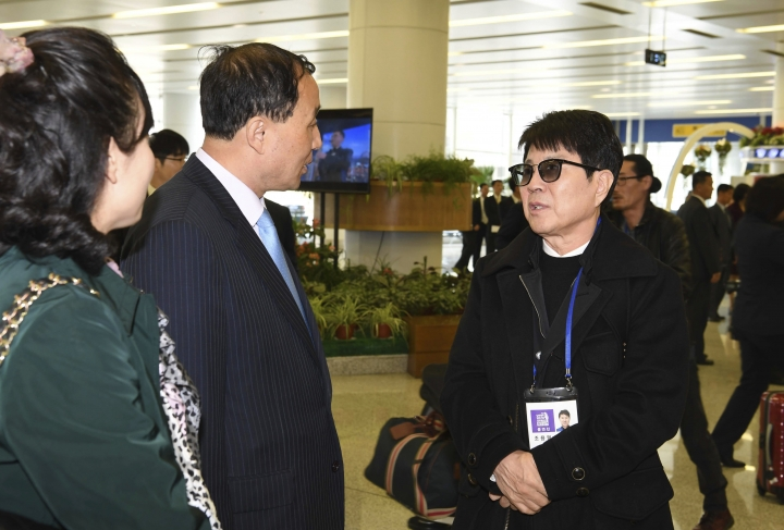 South Korean singer Cho Yong-pil, right, talks with North Koreans at the Pyongyang Airport in Pyongyang, North Korea, Saturday, March 31, 2018. From aging crooners to bubbly K-Pop starlets, some of South Korea's biggest pop stars flew to North Korea on Saturday for rare performances that highlight the sudden thaw in inter-Korean ties after years of tensions over the North's nuclear ambitions. (Korea Pool via AP)
