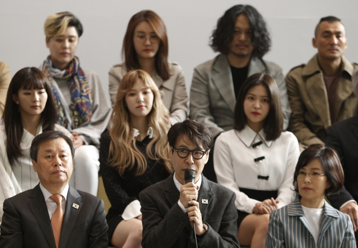 Yun Sang, bottom center, head of South Korea's art troupe, speaks before leaving for North Korea at the Gimpo International Airport in Seoul, South Korea, Saturday, March 31, 2018. A South Korean artistic group including some of the country's biggest pop singers has departed for North Korea for rare performances highlighting the recent warming of ties between the war-separated rivals. (AP Photo/Ahn Youg-joon)