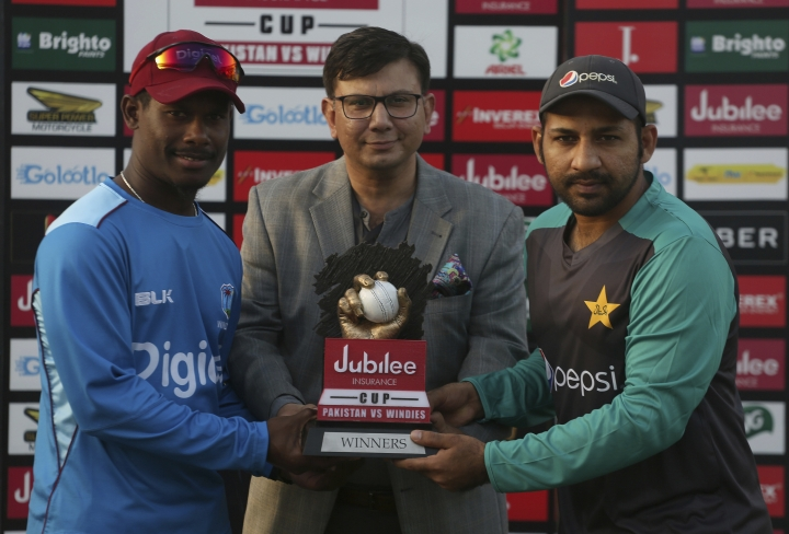 West Indies cricket team's skipper Jason Mohammed, left, and his Pakistani counterpart Sarfraz Ahmed, right, hold the T20 series trophy while posing for a photograph with a representative of Jubilee Insurance company during a ceremony before the 1st of three T20 match between Pakistan and West Indies cricket teams, in Karachi, Pakistan, Sunday April 1, 2018. (AP Photo/Fareed Khan)