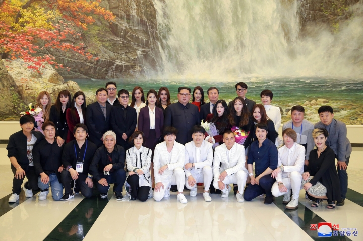 "In this photo provided by the North Korean government, North Korean leader Kim Jong Un, center, poses with his wife Ri Sol Ju, center left, and members of a South Korean artistic group after their performance in Pyongyang, North Korea, Sunday, April 1, 2018. Kim clapped his hands as he, along with his wife and hundreds of other citizens, watched the rare performance Sunday by South Korean pop stars visiting Pyongyang, highlighting the thawing ties between the rivals after years of heightened tensions over the North's nuclear program. At center right is South Korean Culture, Sports and Tourism Minister Do Jong-whan. Independent journalists were not given access to cover the event depicted in this image distributed by the North Korean government. The content of this image is as provided and cannot be independently verified. Korean language watermark on image as provided by source reads: ""KCNA"" which is the abbreviation for Korean Central News Agency. (Korean Central News Agency/Korea News Service via AP)"